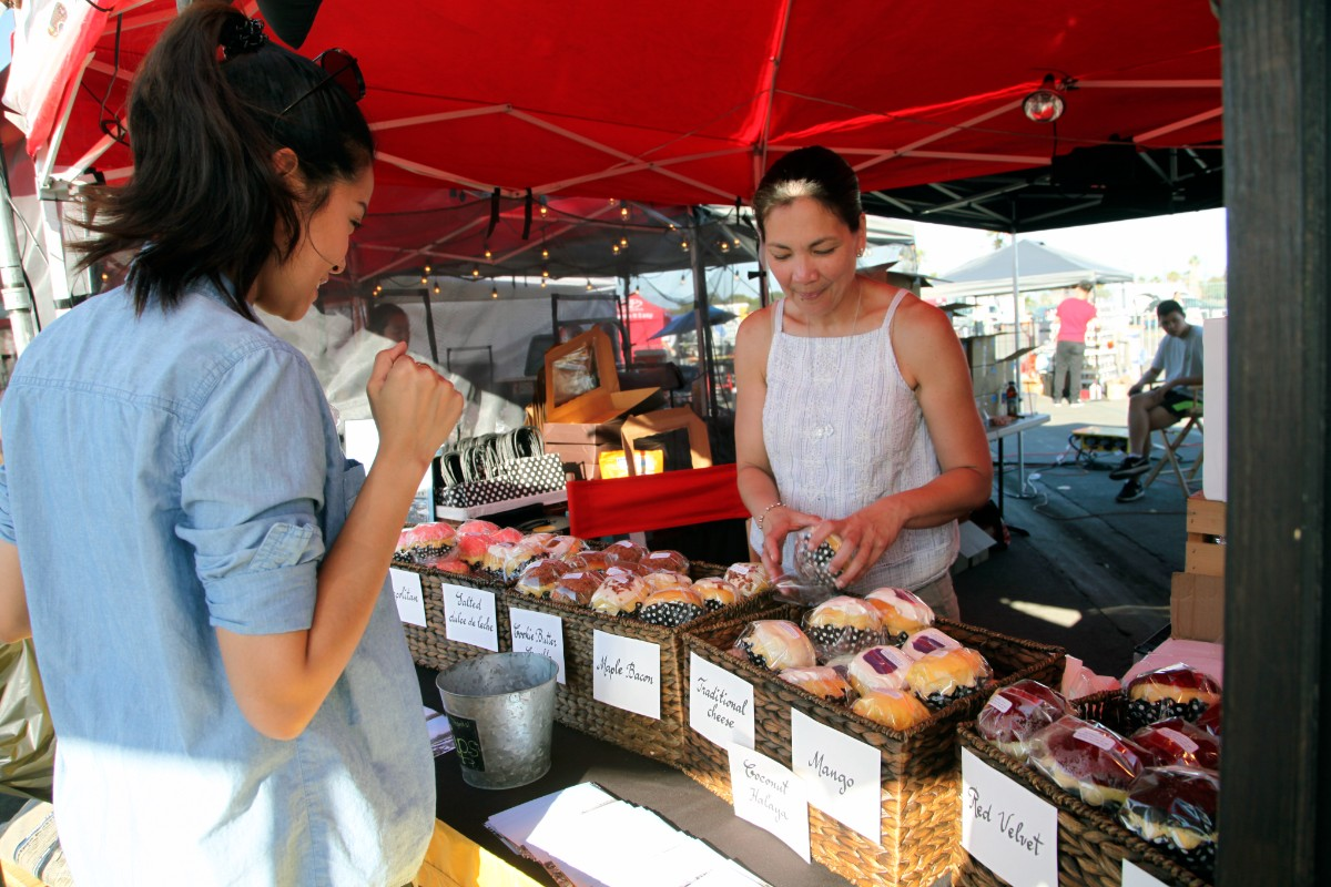 Chari Heredia-Reyes, owner of the Ensaymada Project, sells the brioche bread at the Orange County Night Market on June 16, 2017.
