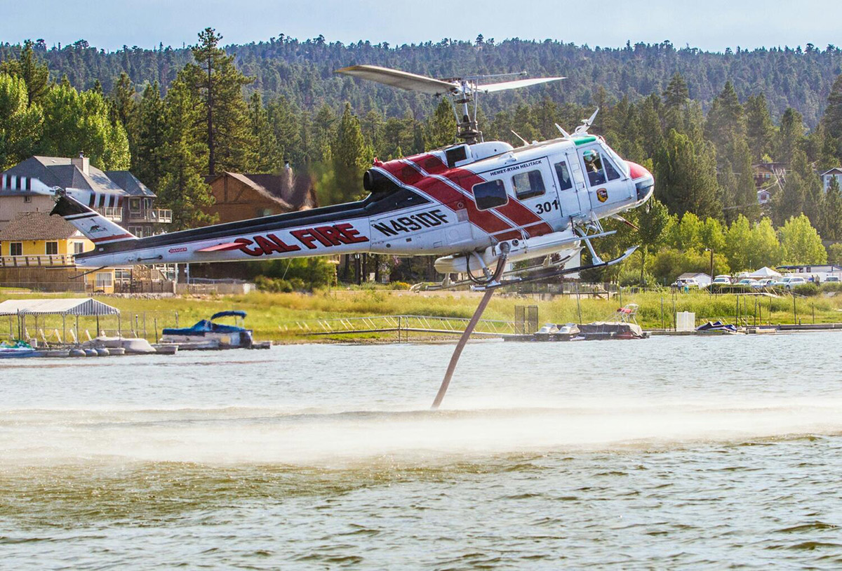 A CAL FIRE helicopter loads water through a snorkel to fill the water tank. | Courtesy of Cliff Walters