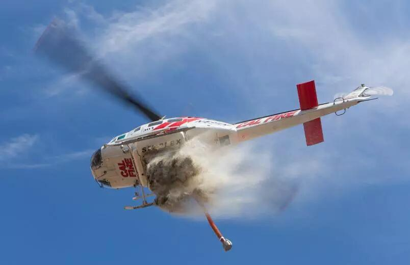 A CAL FIRE helicopter dumps water on a fire. | Courtesy of Cliff Walters