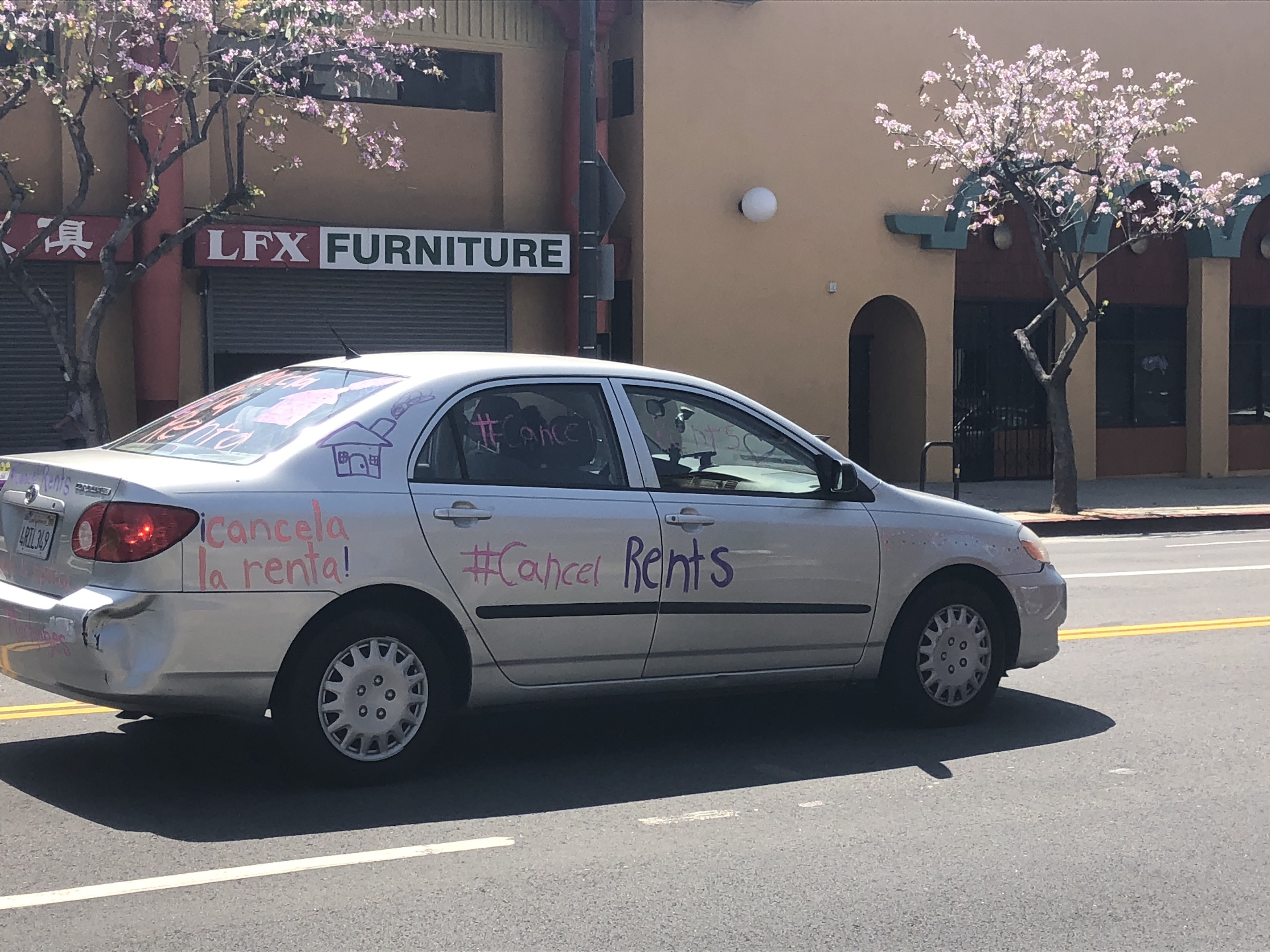 "Car drives in rent relief protest, with paint on sides reading, ""Cancela la renta"" and ""Cancel rents"" 