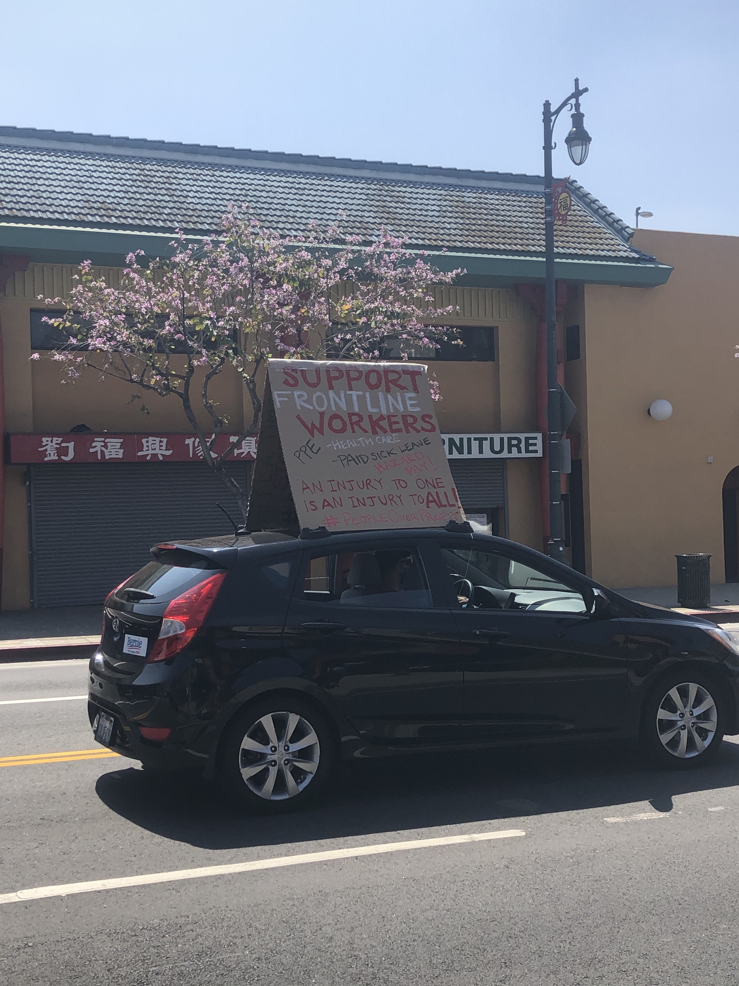 "Sign reading, ""Support frontline workers"" on top of a car, as a part of the rent relief protest in downtown L.A. 