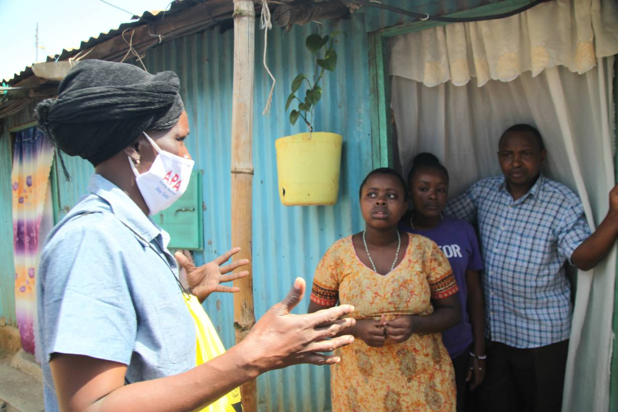 Community health volunteer Everlyne Akinyi Omondi talks to residents about the dangers of COVID-19 in Kawangware informal settlement in Nairobi, Kenya on May 27, 2020. | THOMSON REUTERS FOUNDATION/Nita Bhalla