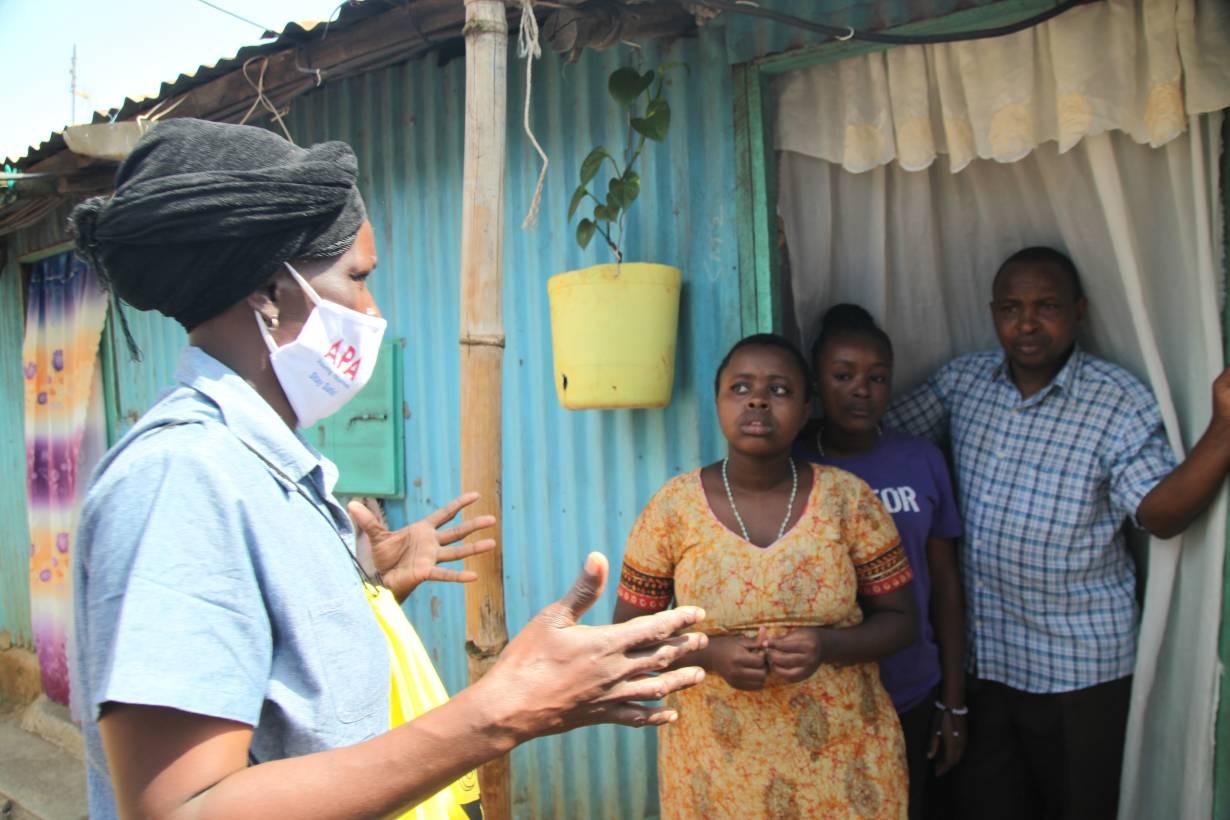 Community health volunteer Everlyne Akinyi Omondi talks to residents about the dangers of COVID-19 in Kawangware informal settlement in Nairobi, Kenya on May 27, 2020.   THOMSON REUTERS FOUNDATION/Nita Bhalla