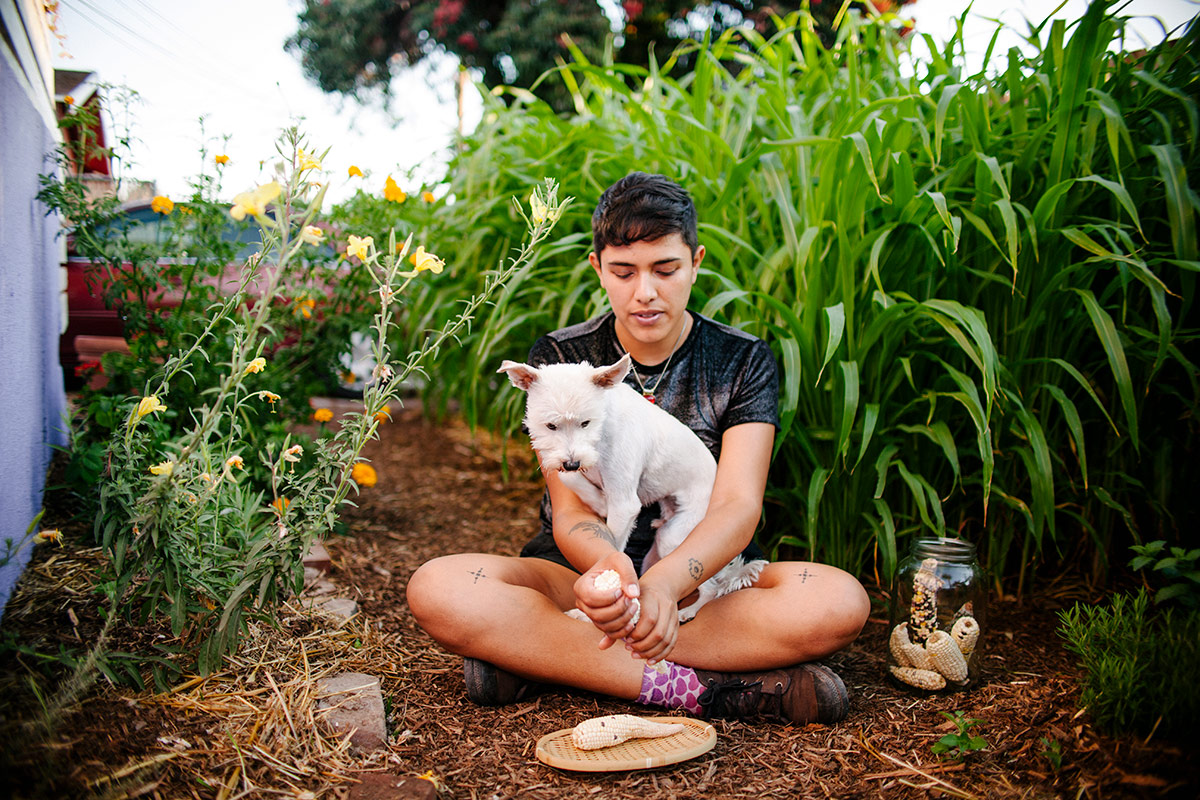 Loba sits in the garden of their East Hollywood home with a white dog. | Samanta Helou Hernandez