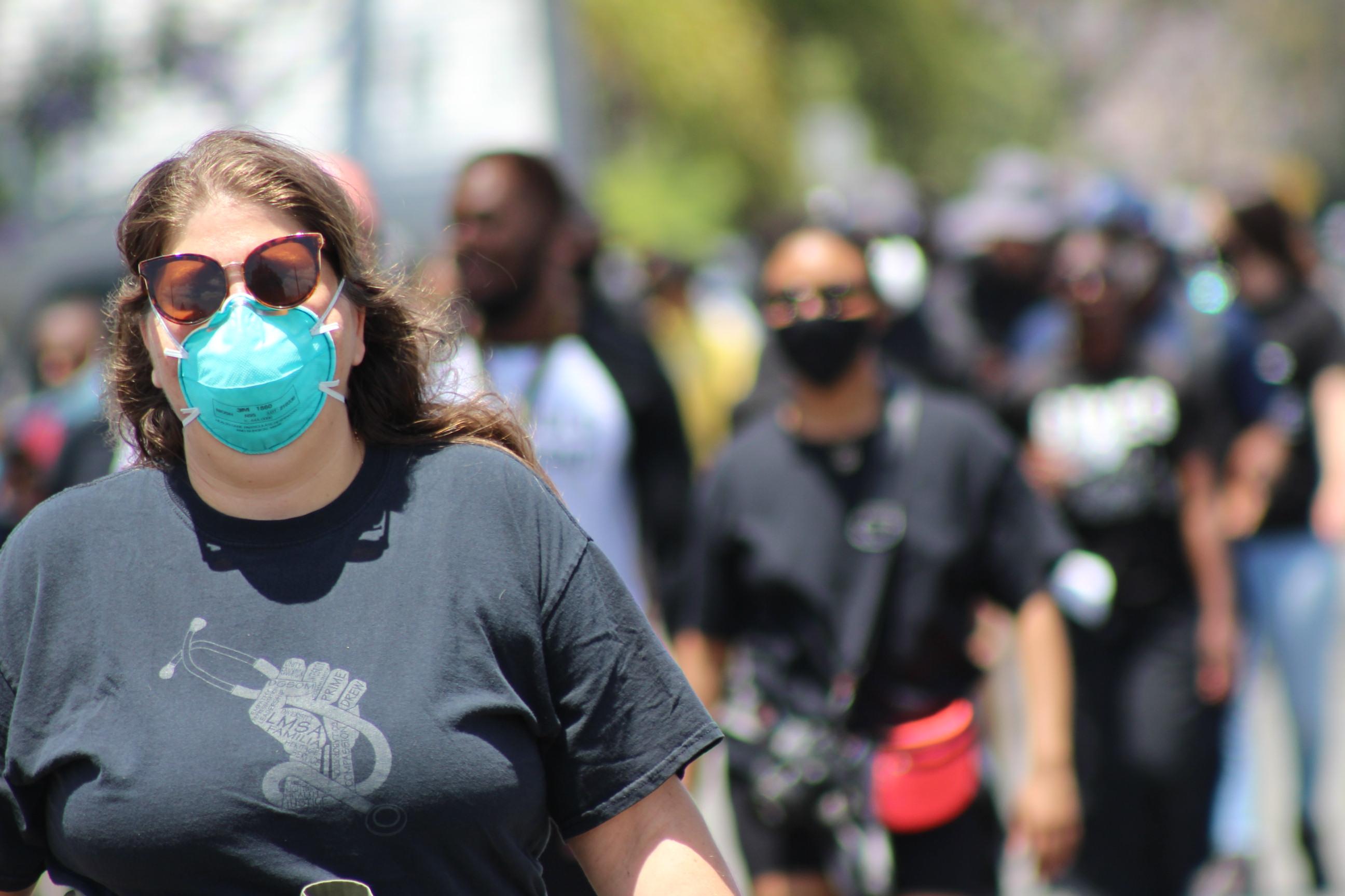 Woman wearing a face mask, walking | Karen Foshay