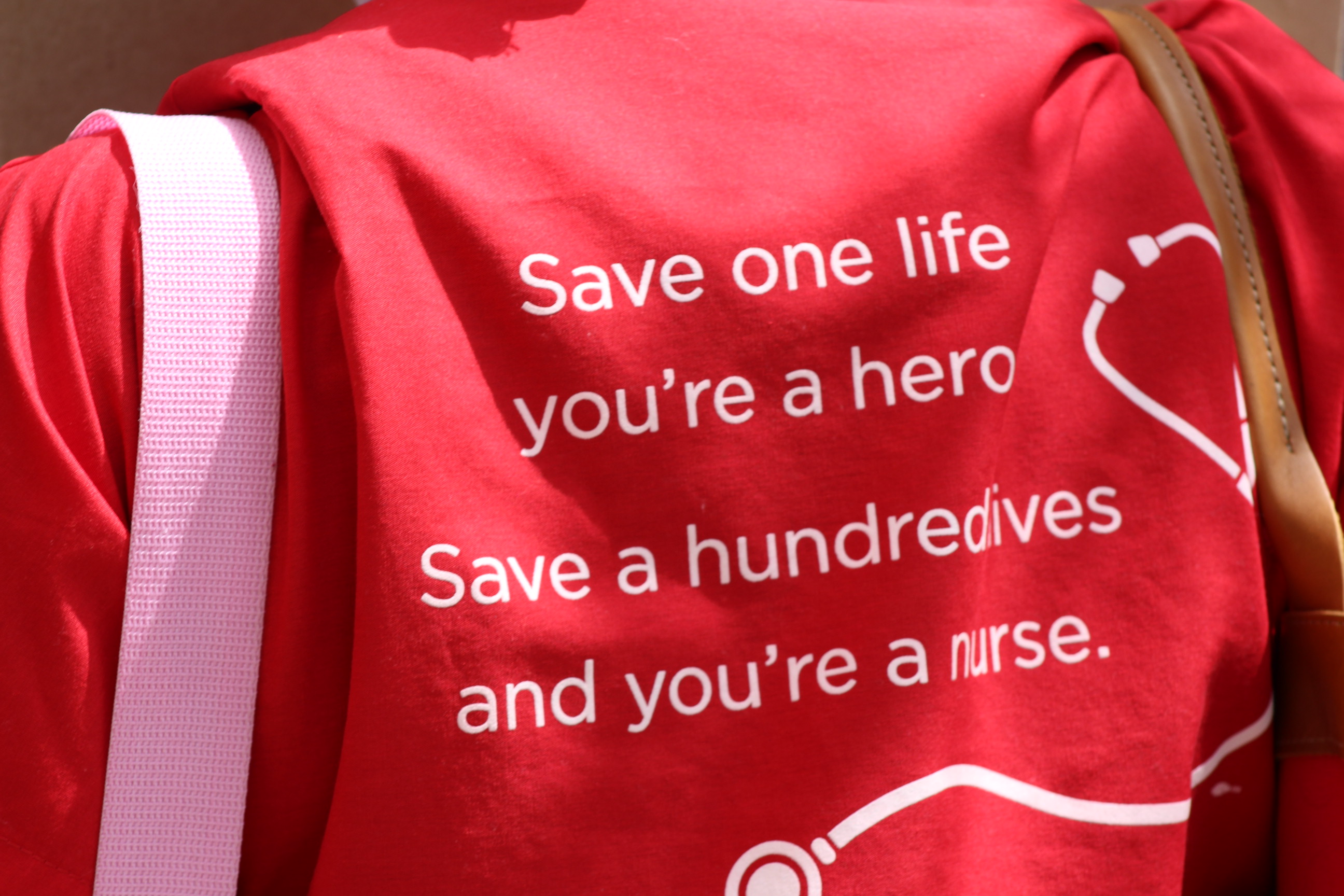 """Back of someone's shirt reading, """"Save one life, you're a hero. Save a hundred lives, you're a nurse"""" during protest on Friday April 3rd 