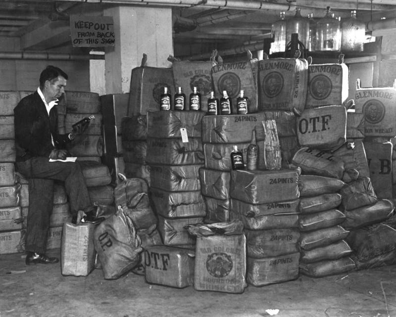 Officer William Barry making inventory of uncut liquor valued at $62,000. | Herald Examiner Collection of the Los Angeles Public Library