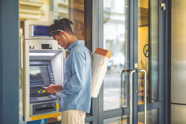 Man wearing a backpack making an ATM transaction. | iStock