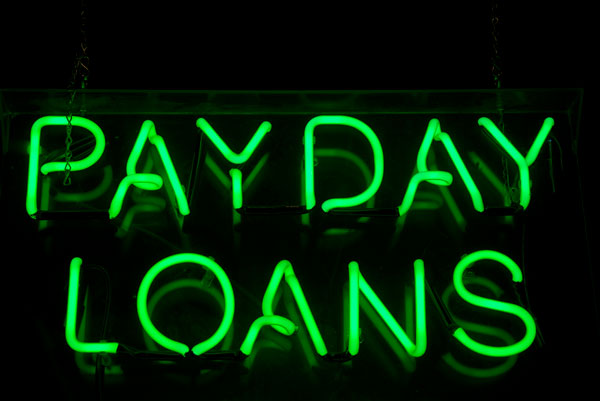 Neon green sign advertising payday loans. | iStock