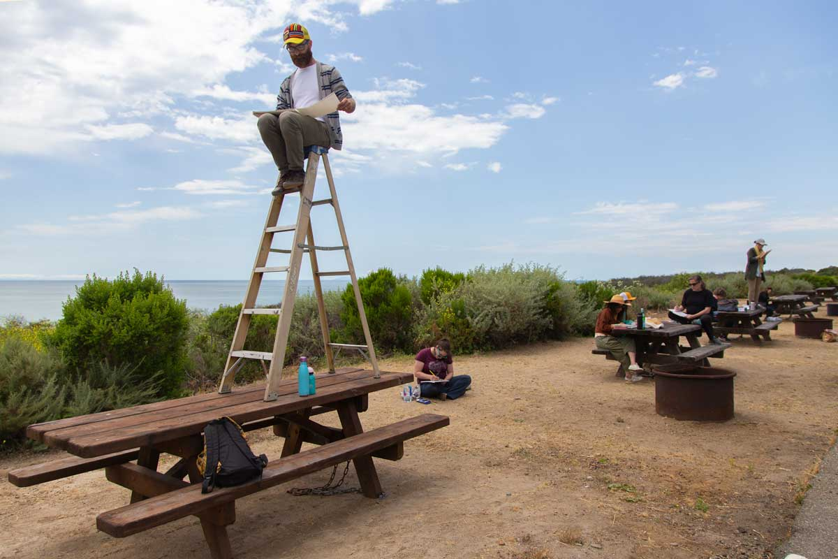 "Nikko Mueller sitting on a ladder on top of a park table at the San Clemente Border Station for ""Three Border Ecologies"" 