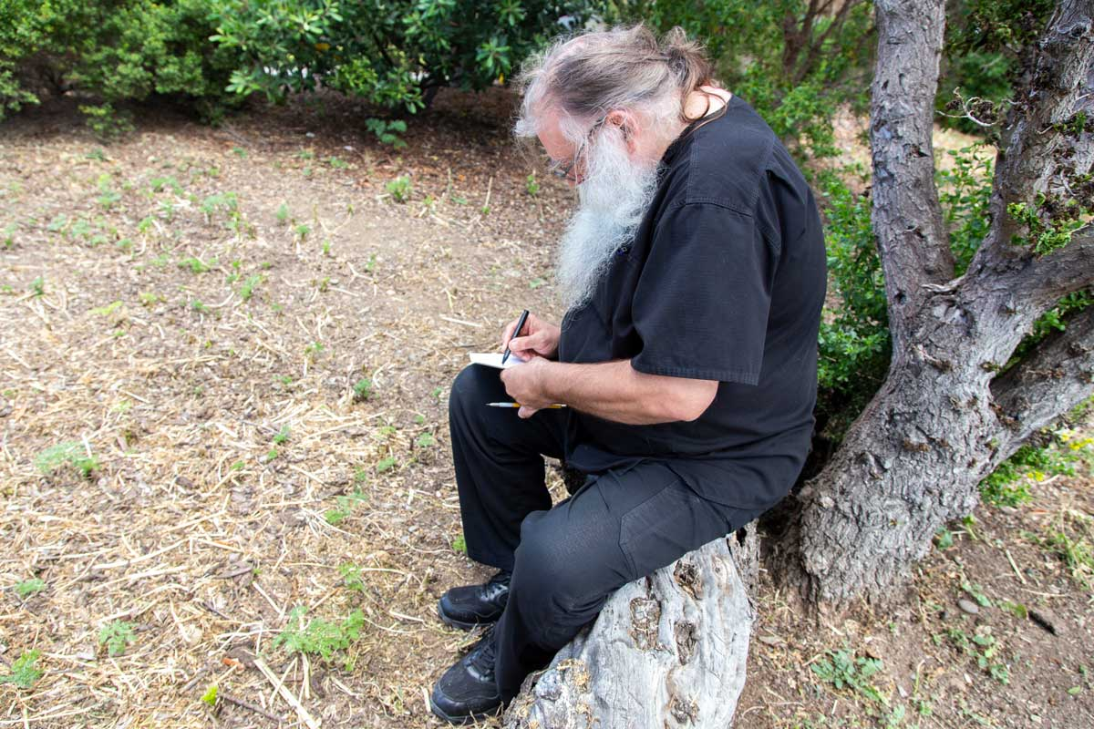 "Thomas Zummer drawing while sitting on a log at San Clemente Border Station for ""Three Border Ecologies"" 