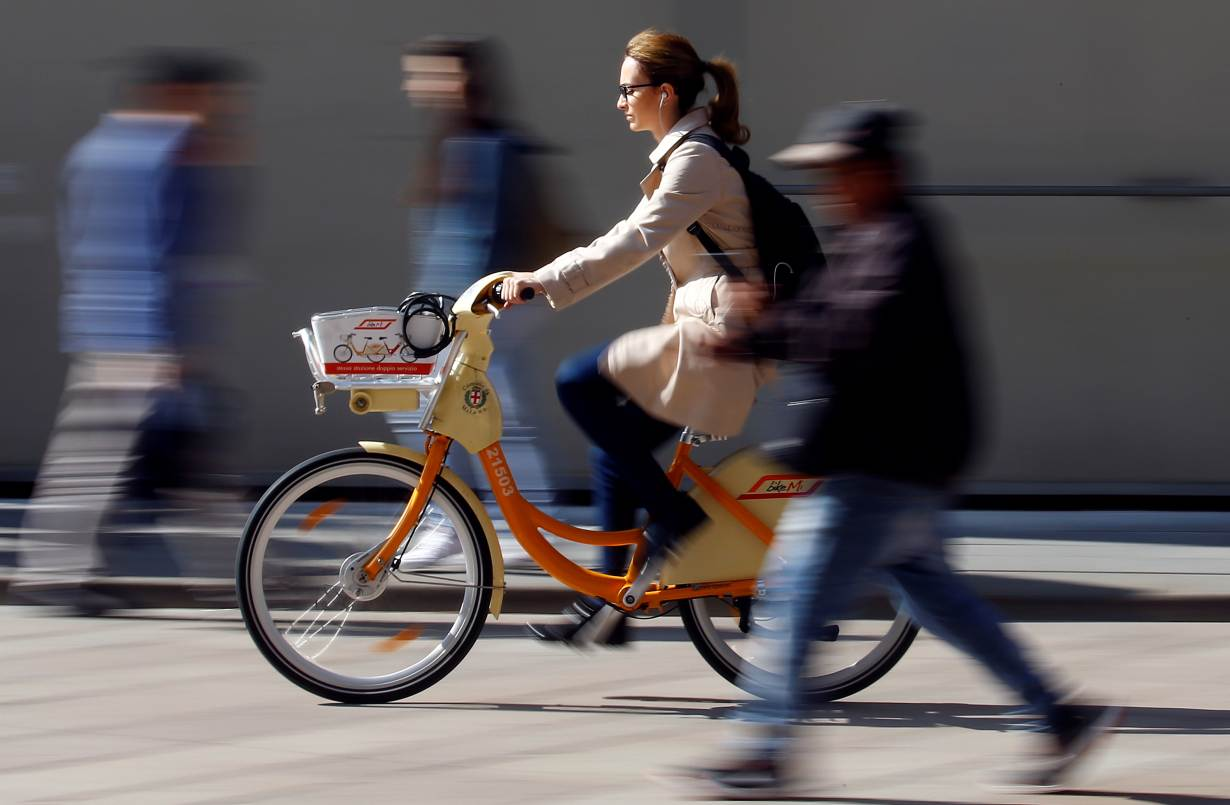 ARCHIVE PHOTO: A woman rides a bicycle from a bike-sharing service in downtown Milan, Italy, May 18, 2018.   REUTERS/Stefano Rellandini