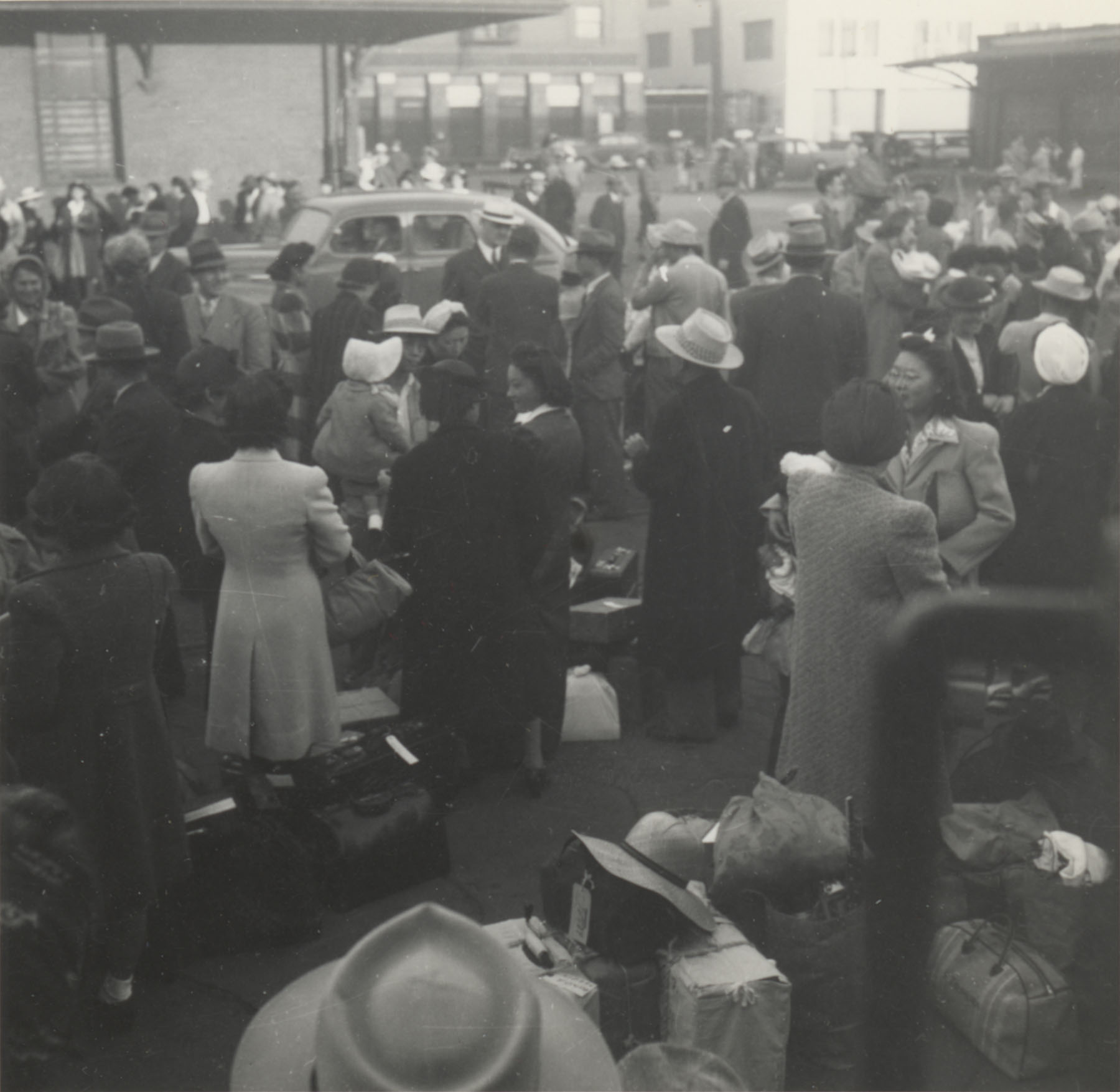 JANM- Japanese Americans wait at a Los Angeles, California, train station. They are bound for Parker, Arizona (Poston concentration camp), May 29, 1942.jpg