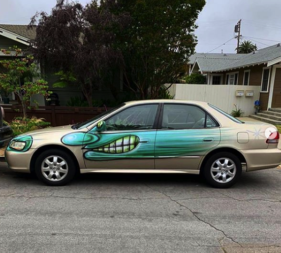 """A beige sedan bombed by Kenny Scharf for his """"Karbombz!"""" project 
