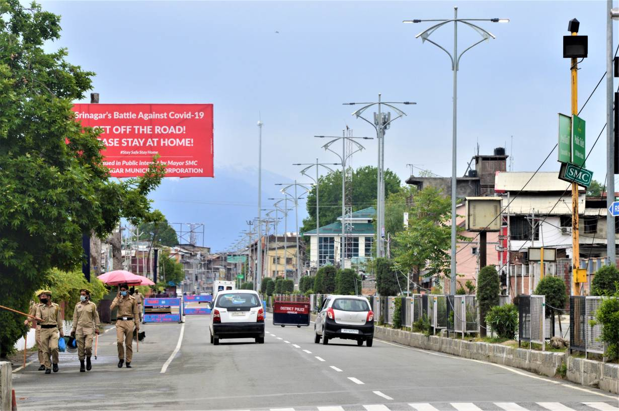 Policemen walk past a sign about COVID-19 in Srinagar, India, May 11, 2020 | Thomson Reuters Foundation/Athar Parvaiz