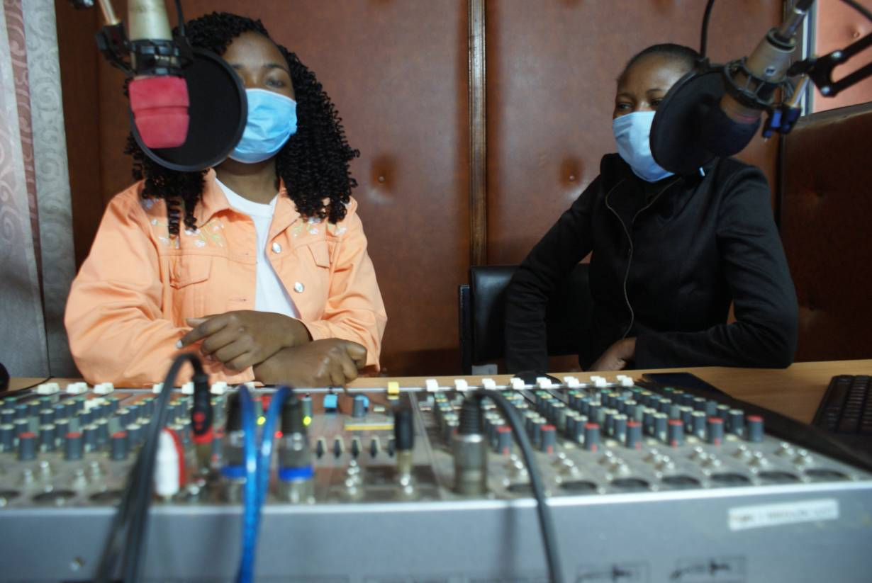 Joyce Wachira (left), a producer at Kangema RANET, and her colleague work at the radio station's studio in Kangema, Kenya, on July 31, 2020. | Thomson Reuters Foundation/Kagondu Njagi