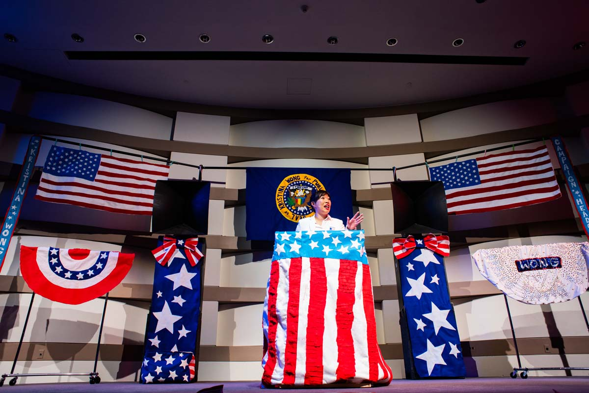 """""""Kristina Wong for Public Office"""" showcases an entire campaign rally set, including an American flag and presidential seal, are sewn 