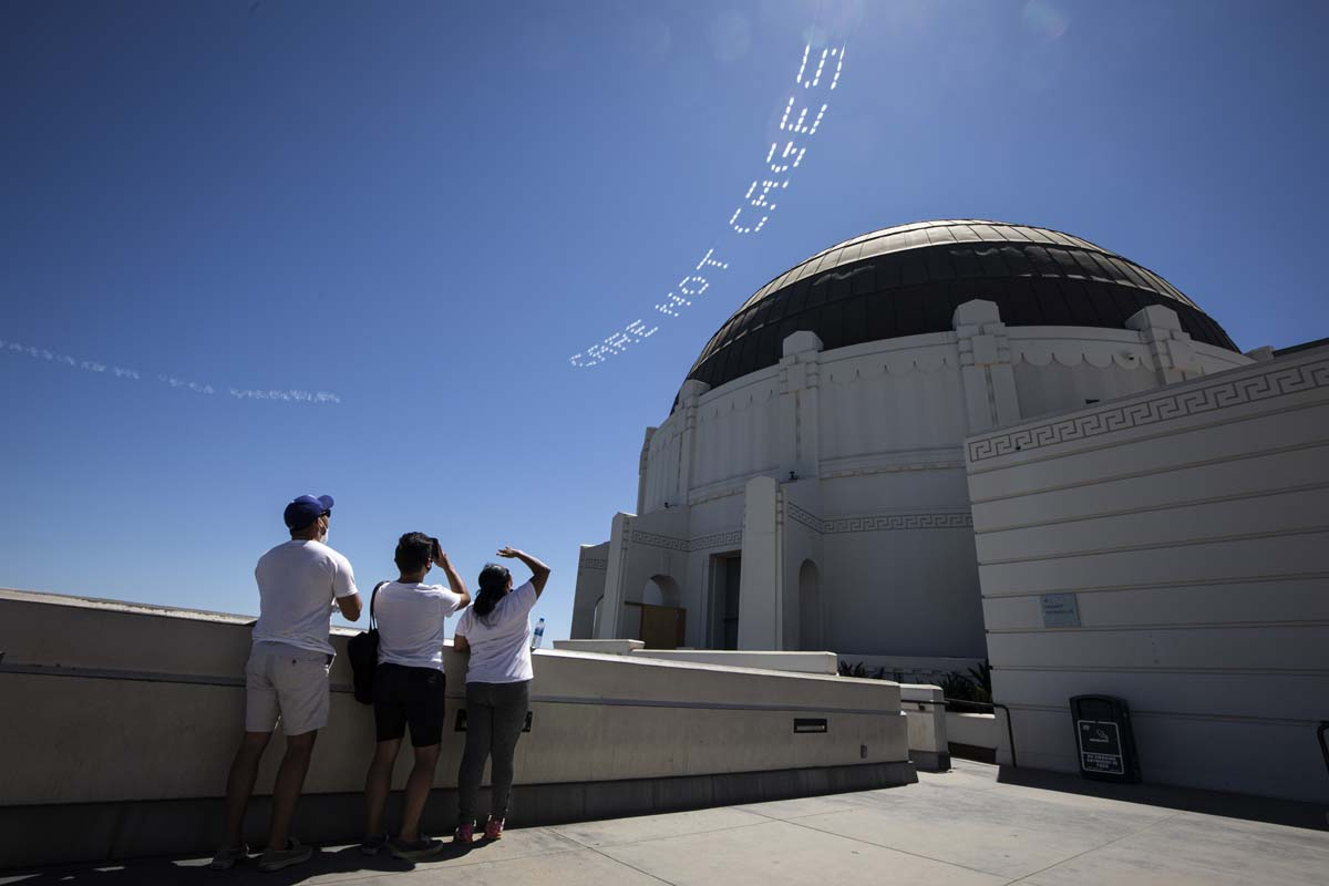 """""""CARE NOT CAGES"""" written in in the sky, contributed by Patrisse Cullors, over the L.A. County Jail as seen from Griffith Park 