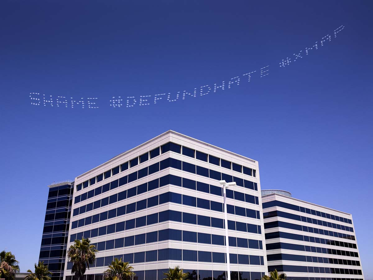 """""""SHAME #DEFUNDHATE #XMAP"""" written in in the sky, contributed by Cassils over the Geo Group Headquarters. The company is one of the largest operators of adult detention centers for ICE.