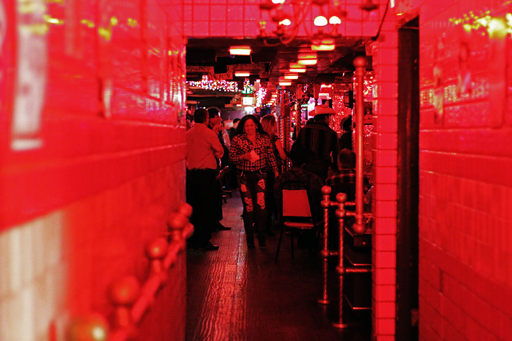 A woman walks toward a hallway under red lights.