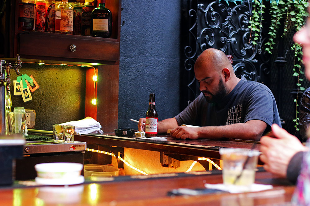 A man sits at the La Cita bar with a cigarette and a Budweiser.