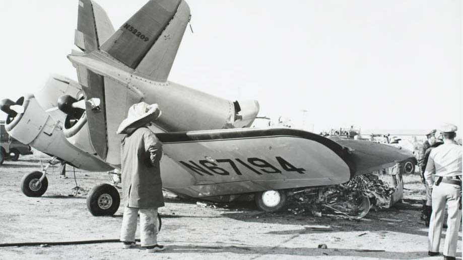 Small plane damaged by crash, with tail broken off and resting on wing.  Cockpit and propellor remain intact.  Firefighter in full-cover protective dress surveys scene with police officer near plane. | John J. Lloyd, Courtesy of CSUDH
