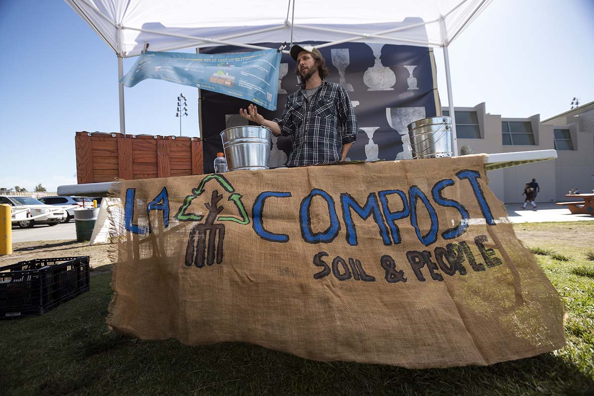 """A man stands behind a stall with the words """"L.A. Compost"""" while rehearsals of """"ALL AGAIN"""" goes on. The event was organized by Carolyn Pennypacker Riggs and Annie Gimas 