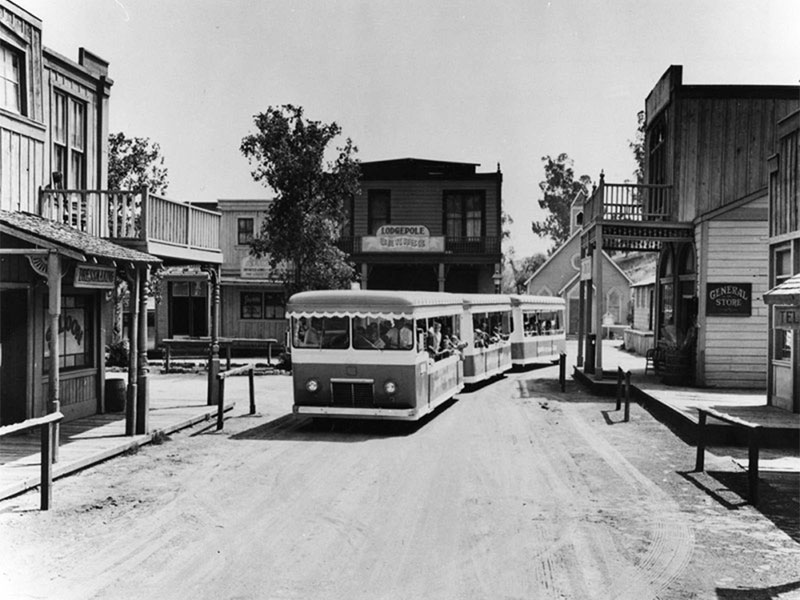 A tour bus moves through the backlot western sets of Universal Studios | Security Pacific National Bank Collection at Los Angeles Public Library