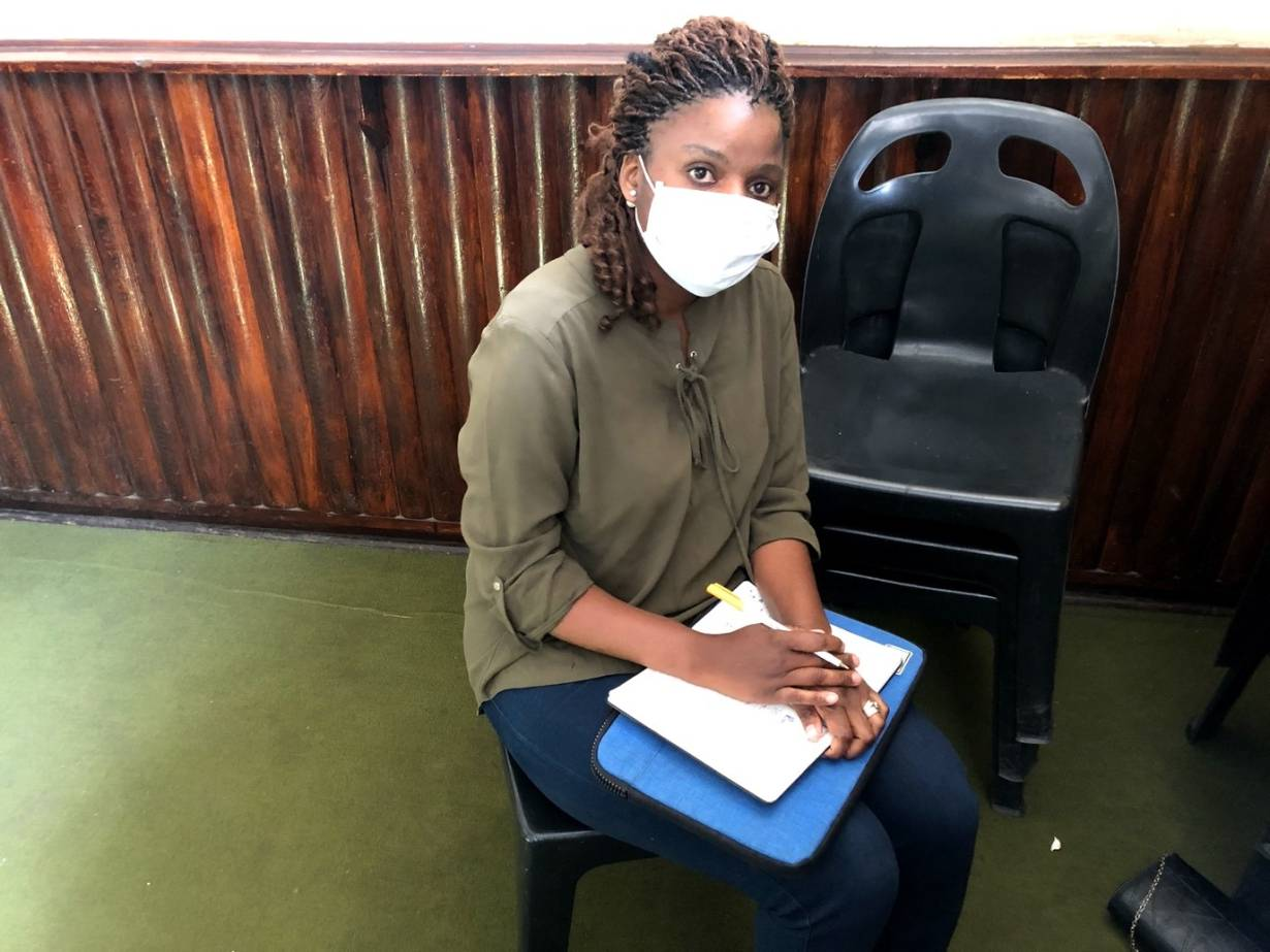 Sithandekile Mlauzi, 29, a VSO volunteer sits with her notebook and tablet on her lap in Bulawayo, Zimbabwe. 11 July 2020. | Thomson Reuters Foundation/Lungelo Ndlovu
