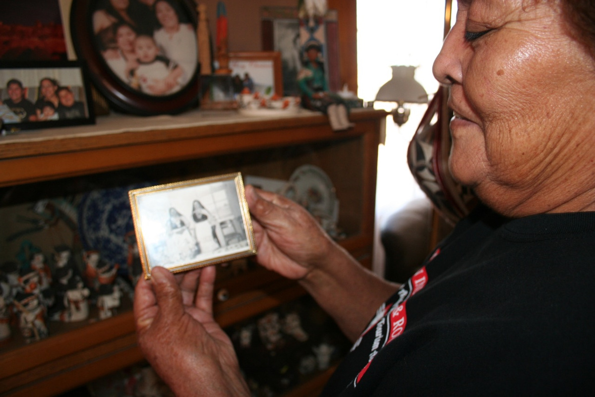 Pueblo of Acoma elder Mary Lowden holds a photo of her mother and her aunt, both pottery makers. As  a girl, Mary and her sisters would walk down to the highway to sit at the general store and sell the  pottery they helped make.