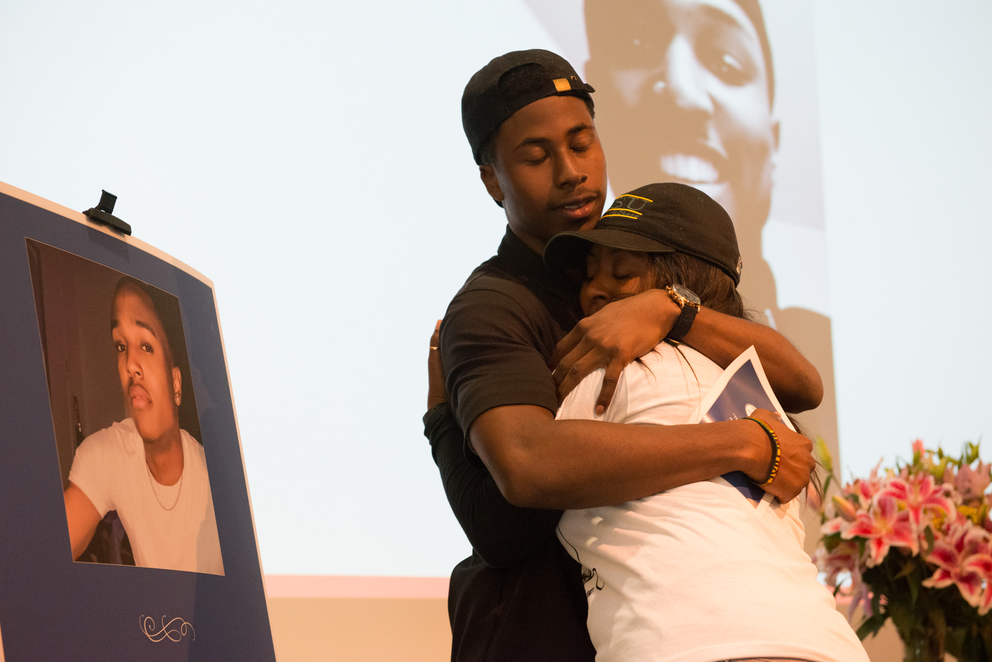 "Two people hugging at memorial with photo of deceased next to them | Still from SoCal Connected, ""Who Killed Josiah?"", Courtesy Mark McKenna"