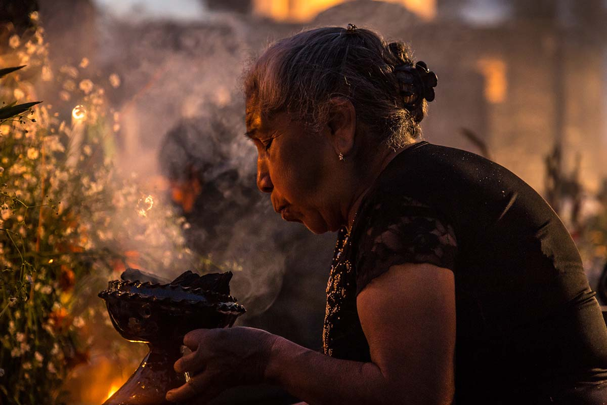"Woman lighting copal incense at the cemetery during the ""Alumbrada"" vigil in San Andrés Mixquic 