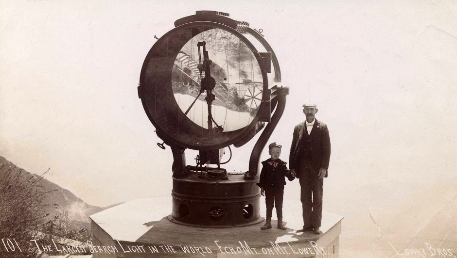 A man and child stand next to the Echo Mountain searchlight