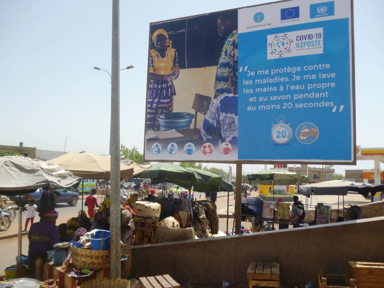 """A public health advertisement to prevent the spread of coronavirus on a street in Bamako, Mali, May 21, 2020. The sign says: """"I protect myself from illnesses. I wash my hands with clean water and soap for at least 20 seconds."""" Thomson Reuters Foundation/S"""