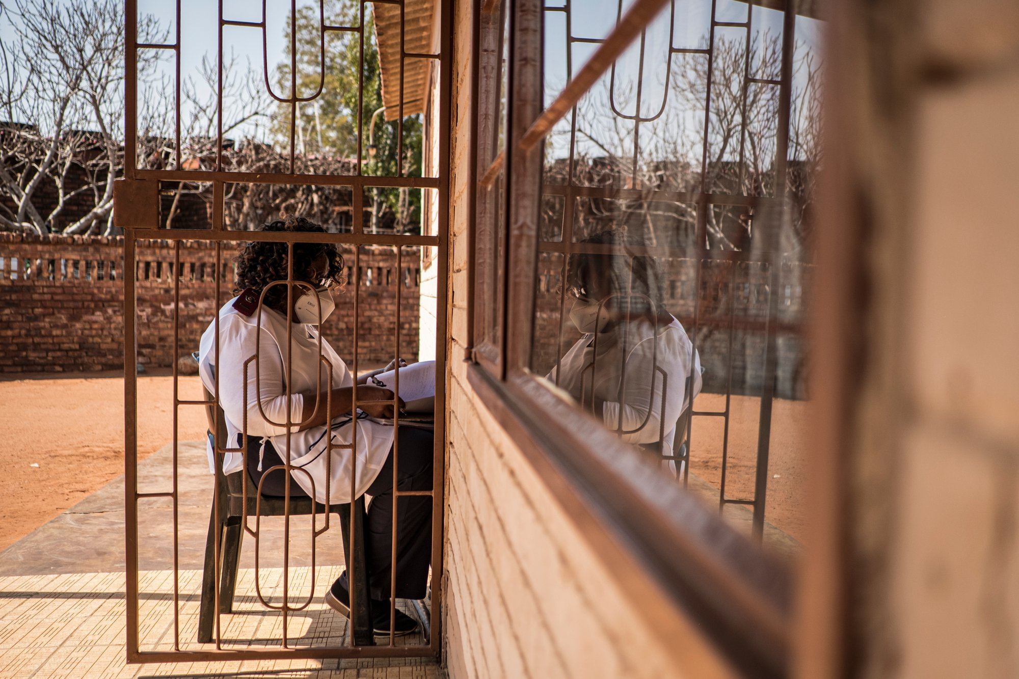 Sister Rachel Asitile (61) is pictured sitting, in accordance with social distancing measures, outside the home of a patient who tested positive for COVID-19 to do a follow up assessment.   Thomson Reuters Foundation/Gulshan Khan