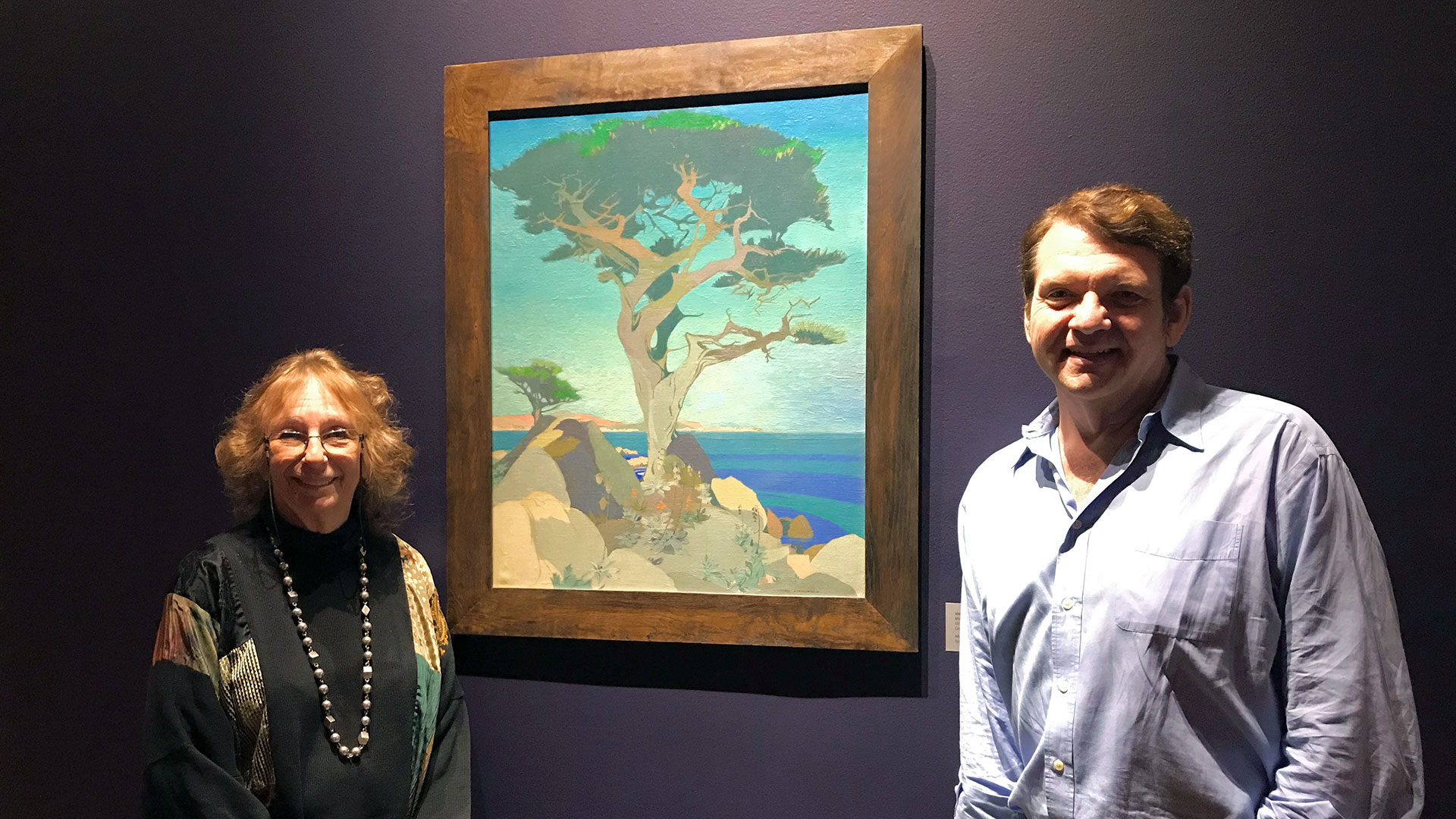 "Exhibition Curator Maurine St. Gaudens and Co-Curator Joseph Morsman with Vivian Stringfield's painting ""Monterey Cypress,"" circa 1925 exhibited in Something Revealed at the Pasadena Museum of History 