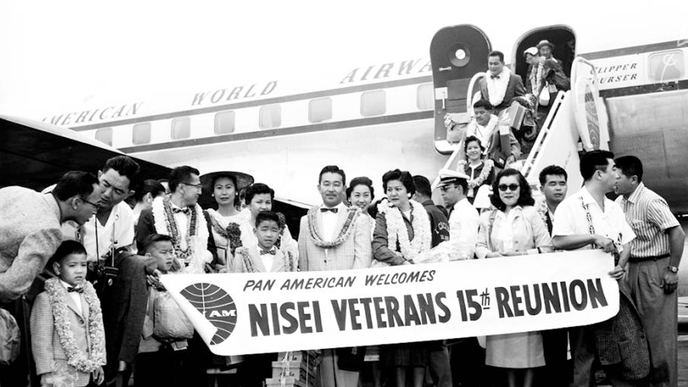Nissei welcome of 442nd Go for Broke Division during a Nissei Veterans reunion, 26 July 1958. In the photo are Hatsumi Mitsunaga (Miss Reunion); Fred Ida; Togo Nakagawa; Paul Bannai. | Go for Broke National Education Center Collection, USC Libraries