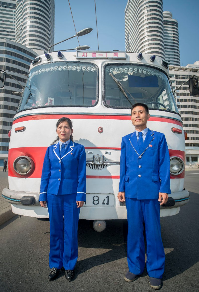 A bus driver and ticket taker stand in front of the historic bus that Kim Il Sung rode on. North Korea | Mark Edward Harris