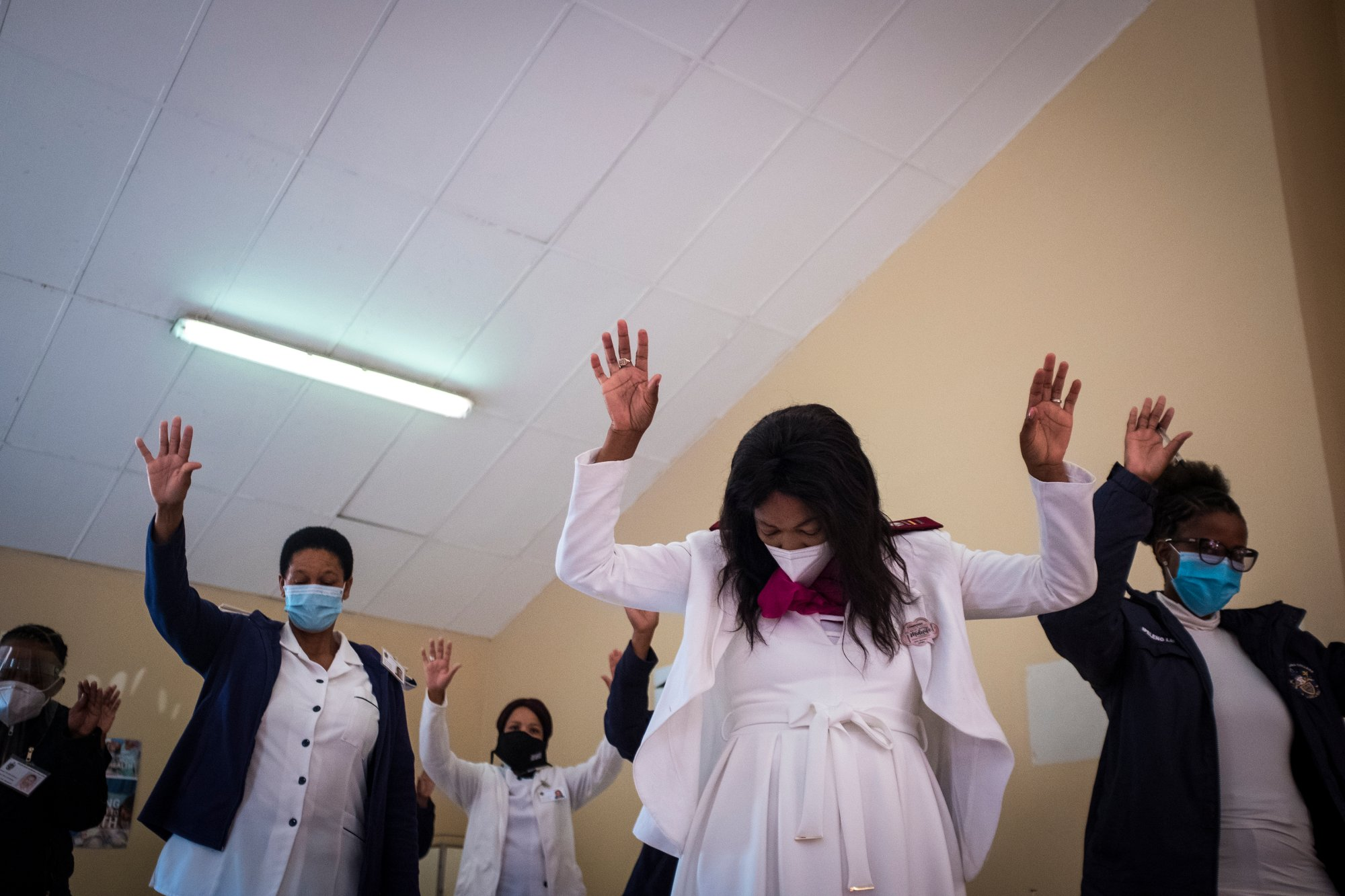 """Nurses raise their hands in prayer during an event in honor of the World Health organisation's (WHO) """"Year of the Nurse"""" 