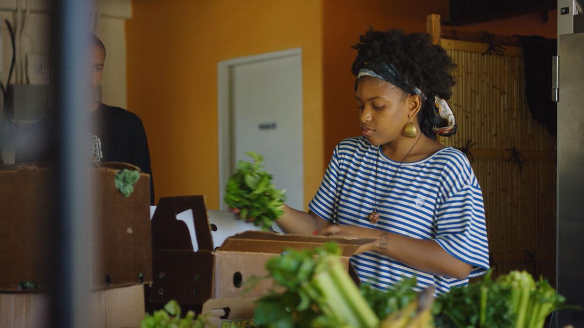 "Olympia Auset arranging produce | Still from ""Broken Bread"" Access"