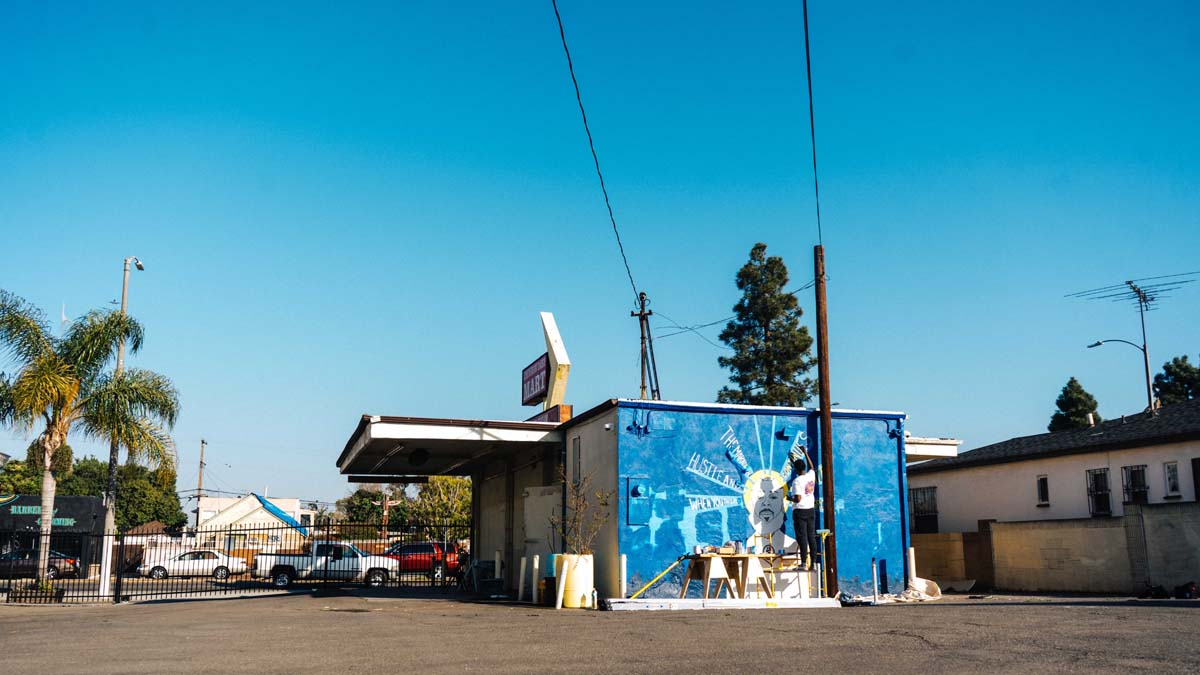 "A wide shot of the Crenshaw Dairy Mart showing artist Oto-Abasi Attah painting a mural of Nipsey Hustle, ""Saint Nip"" 