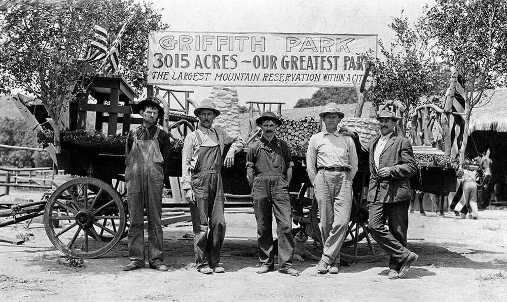 "A group of men stand before a wagon and a painted banner with reads, ""Griffith Park, 3015 acres — Our greatest park. The largest mountain reservation within a city."" 
