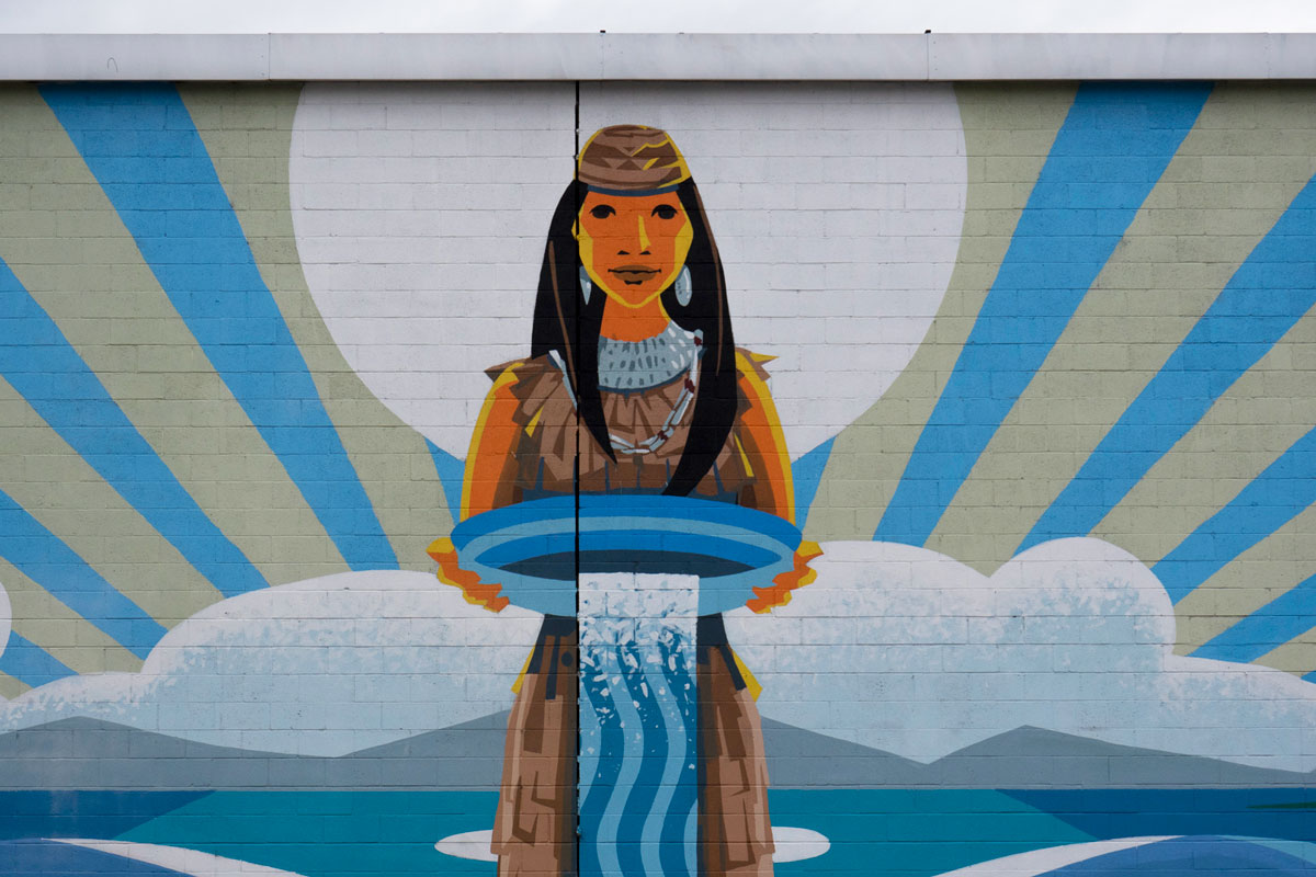 """Rushing Waters"" mural in Pacoima. The image shows a Native American woman holding a basin of water. 