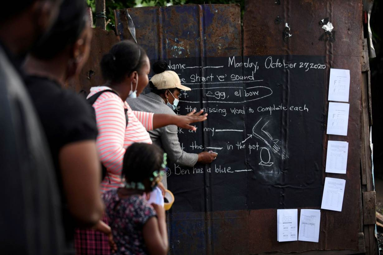 Educator Taneka Mckoy Phipps writes a lesson on a blackboard painted on a zinc fence, in a low-income neighbourhood, during the coronavirus disease (COVID-19) outbreak in Kingston, Jamaica October 27, 2020. October 27, 2020. | REUTERS/Gladstone Taylor