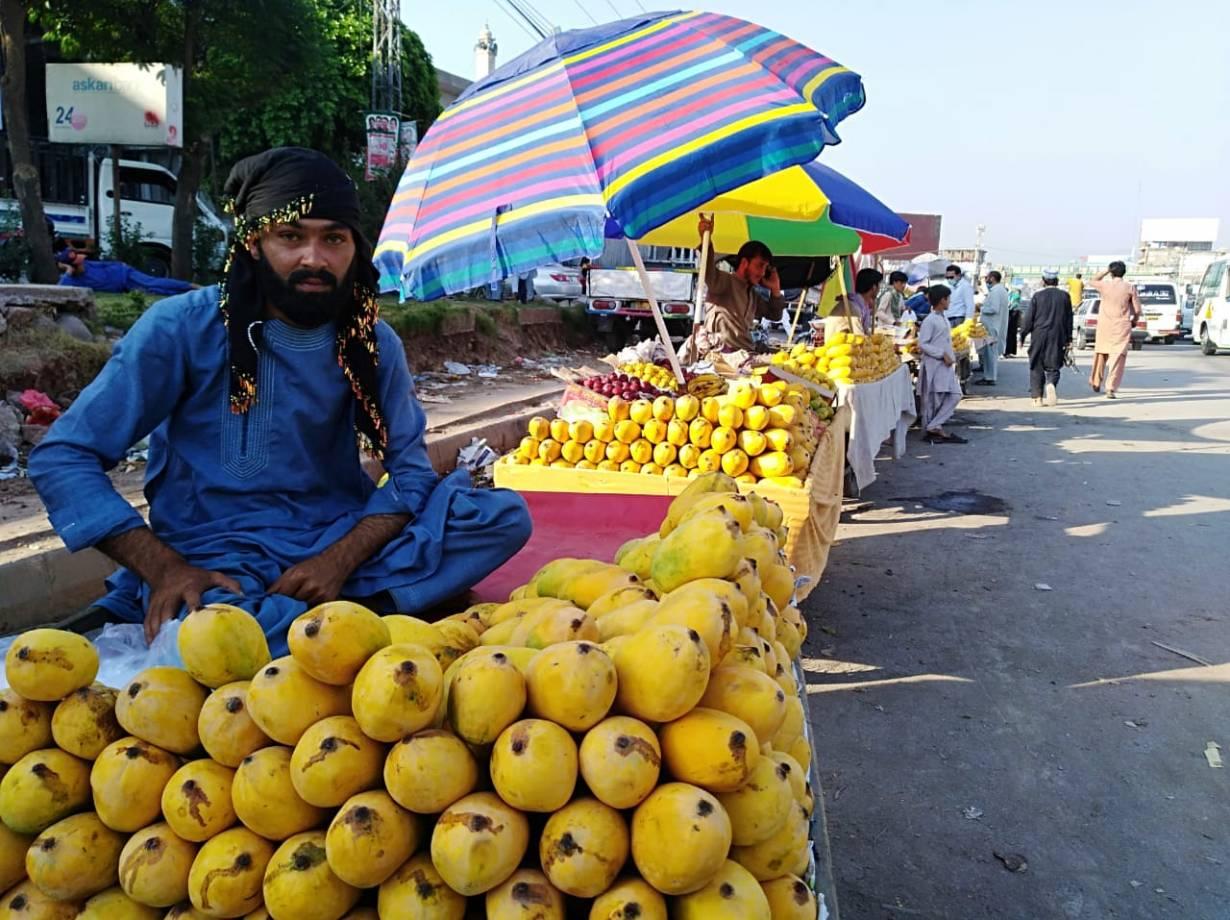 Mango vendors wait for customers in the Barakahu area of Islamabad, Pakistan's capital, on June 16, 2020. | Thomson Reuters Foundation/Peer Muhammad