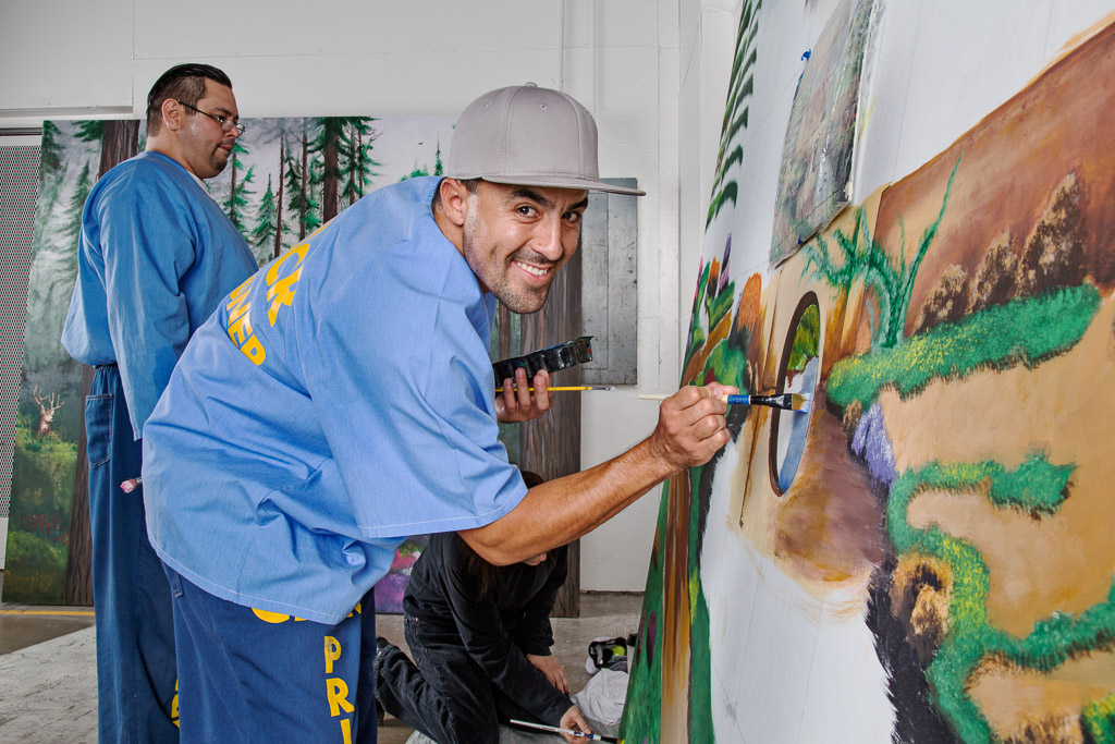 A prison inmate paints a mural as part of a Project PAINT art workshop at Richard J. Donovan Correctional Facility in San Diego