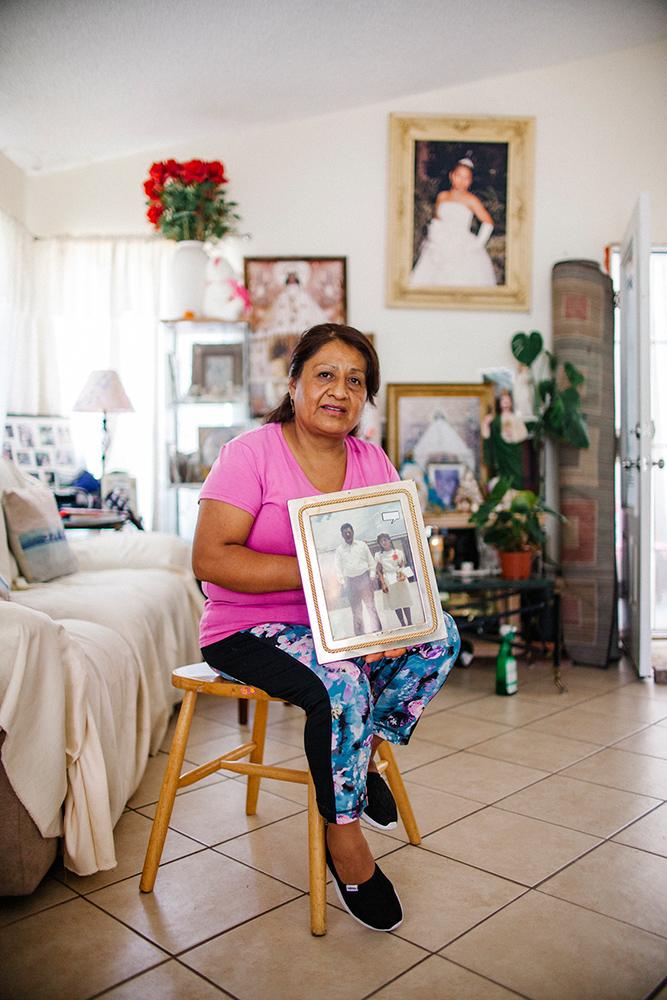 Reyna Garcia at home with a family photo.   Samanta Helou Hernandez