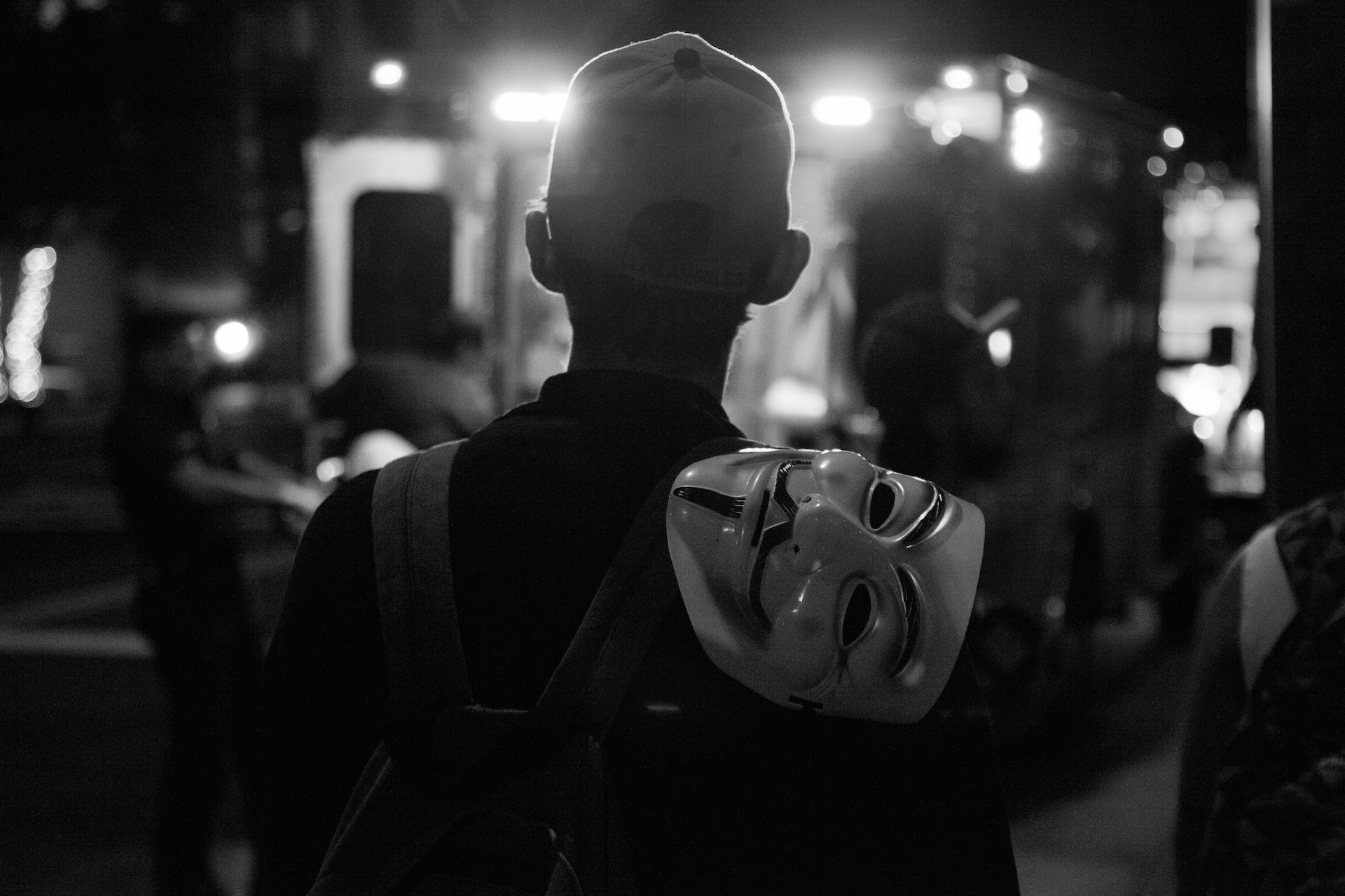 Man with Guy Fawkes mask over his shoulder | Rafael Cardenas