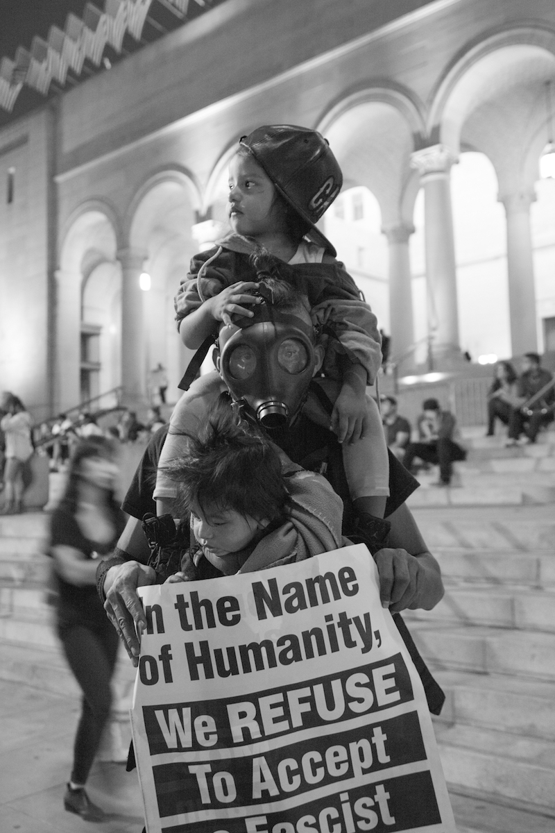 Man in gas mask with two children and a protest sign | Rafael Cardenas