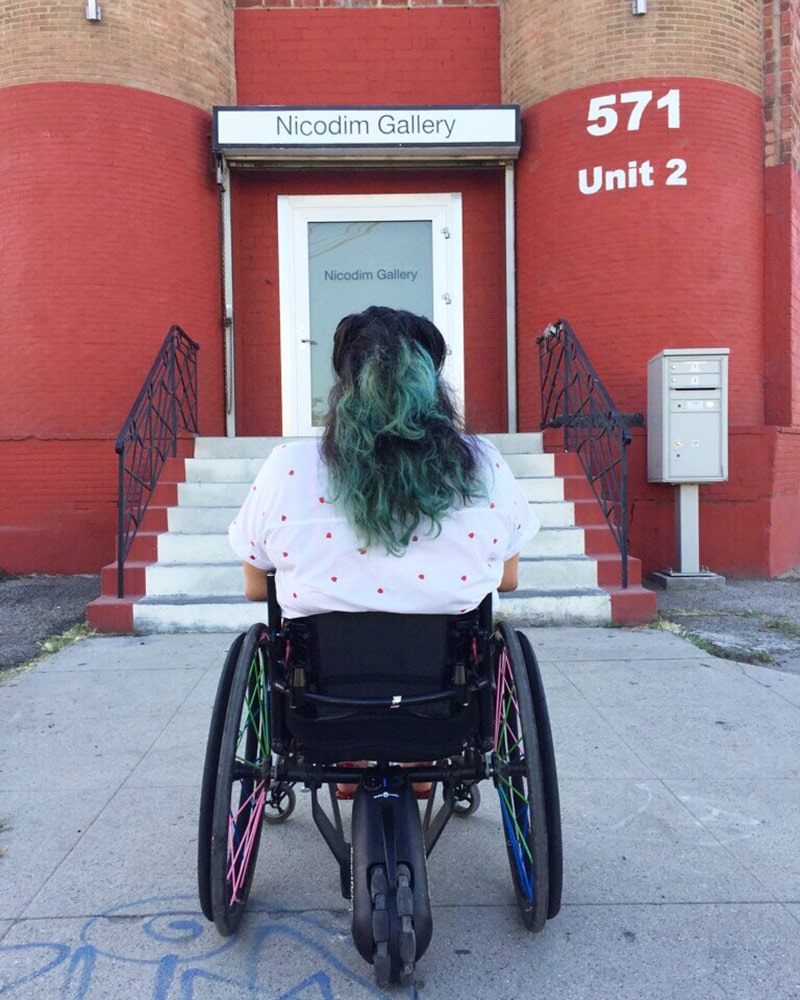 """Jaklin Romine sitting in her wheelchair in front of a closed door with stairs leading up to it. Still from video performance at Los Angeles Contemporary Archive of """"Access Denied"""" by Jaklin Romine, 2015. 